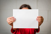 A girl holding up a blank paper