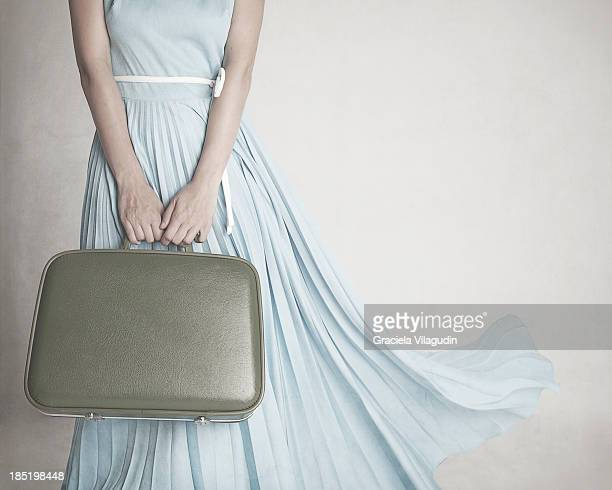 Girl with blue dress holding vintage suitcase