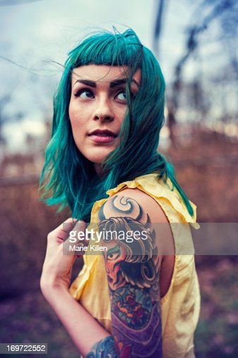 Girl with blue hair and tattoos looking over : Stock Photo