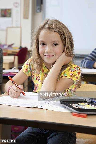 Girl with book in classroom, portrait