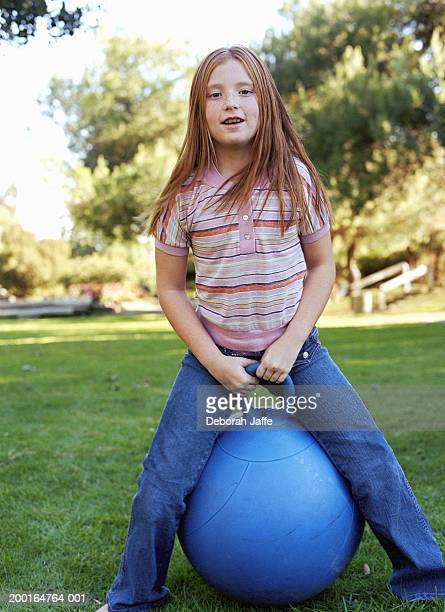 Girl (8-10) with bouncing toy, portrait