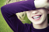 Girl with braces laughing while covering eyes