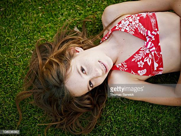 Girl with braces laying on grass smiling