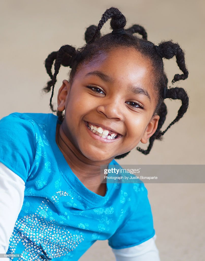Girl with braids and missing tooth : Stock Photo