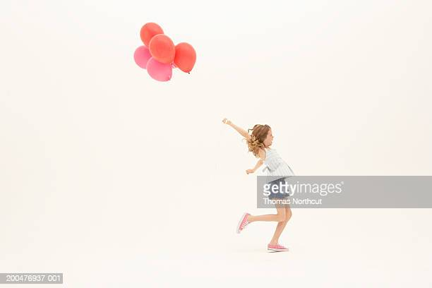 Girl (8-10) with bunch of balloons running, arm raised, side view