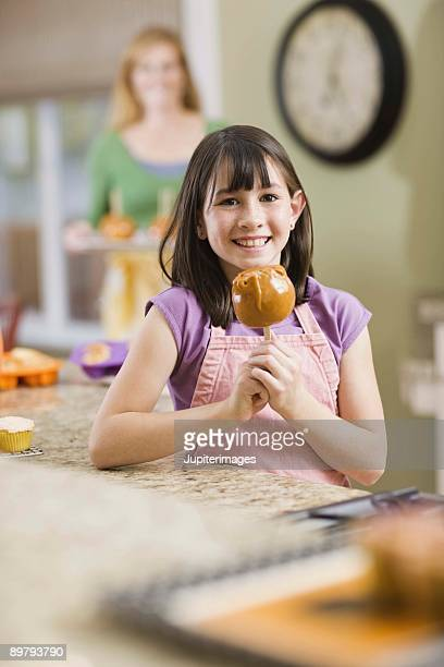 Girl with candy apple in kitchen
