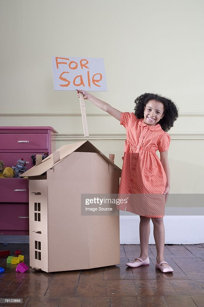 Girl with cardboard house and for sale sign : Stock Photo