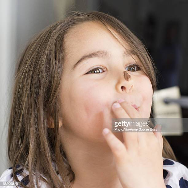 Girl with chocolate smeared on her nose, licking fingers