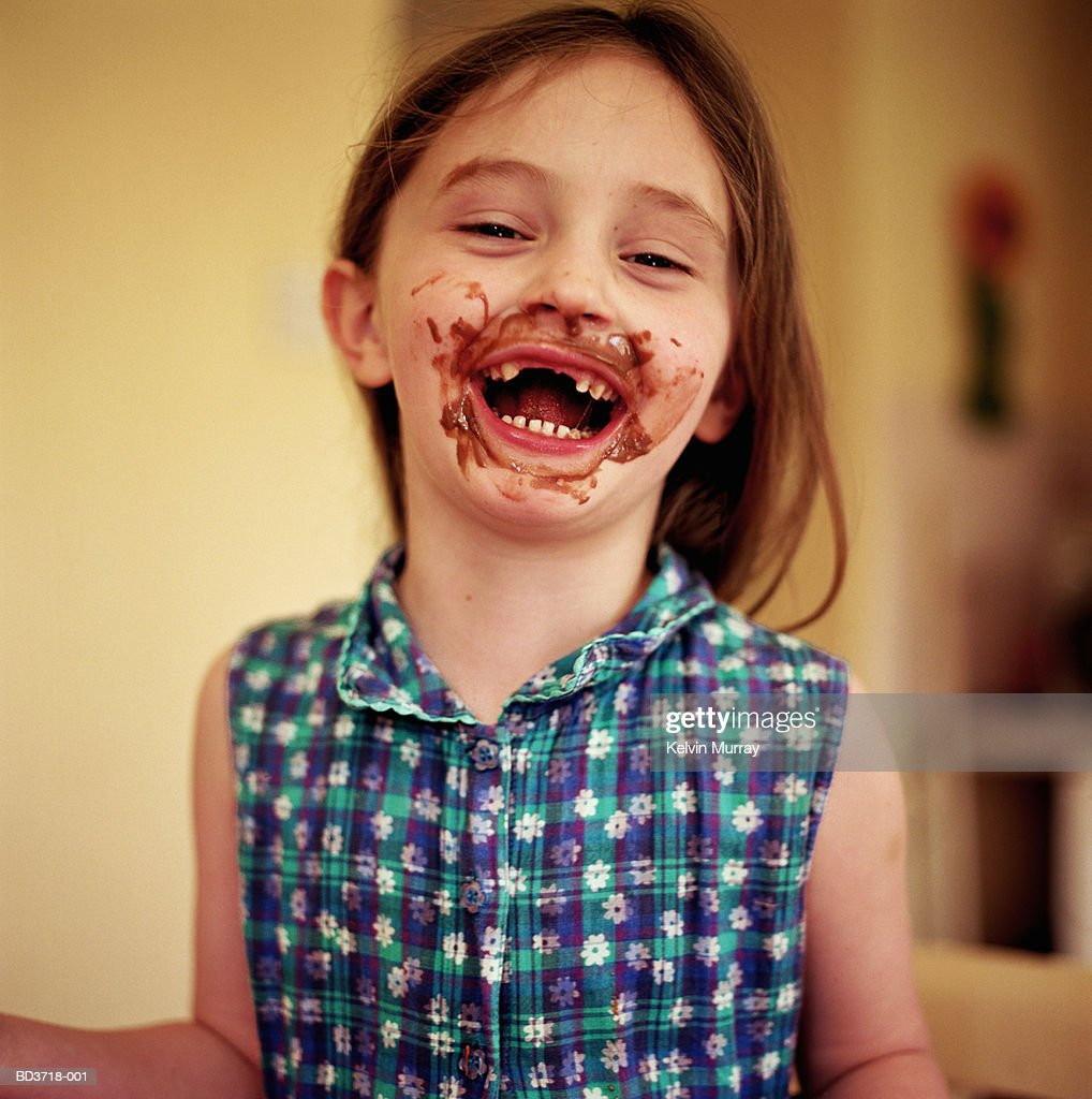 Girl (5-7) with chocolate smeared over face, smiling, portrait : Stock Photo