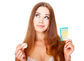 Girl with contraceptives posing against white background