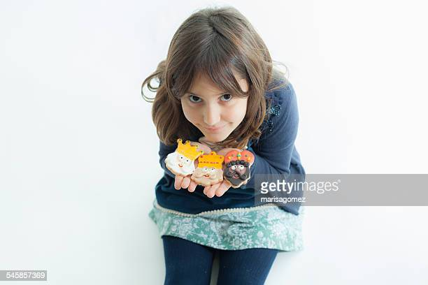Girl (6-7) with cookies on white background