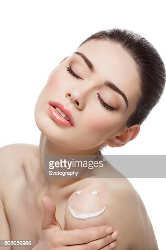 Girl with cream smiley face on shoulder : Stock Photo