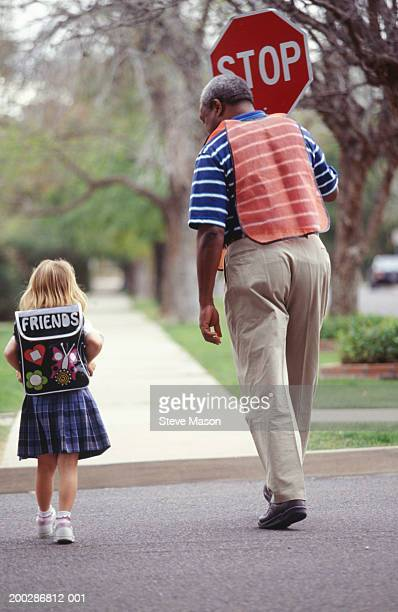 Girl (4-5) with crossing guard, crossing street, rear view