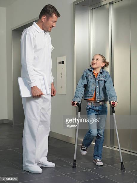 Girl (7-10) with crutches looking up at doctor near elevator