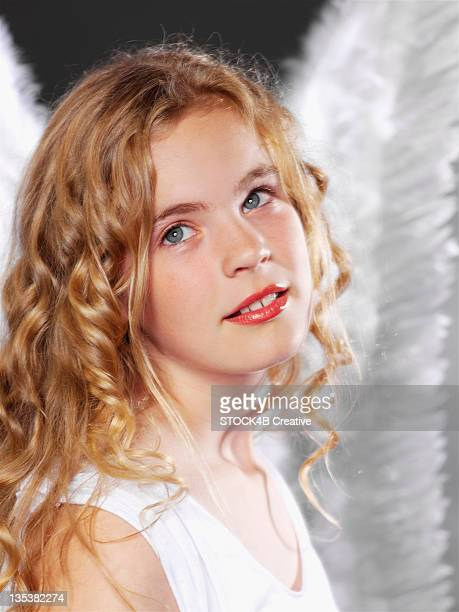 Girl with curly hair wearing angel wings