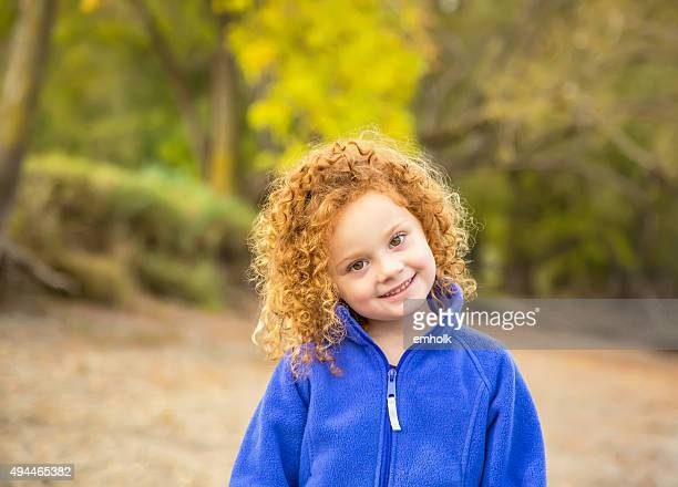 Girl With Curly Red Hair on Riverbank in Autumn