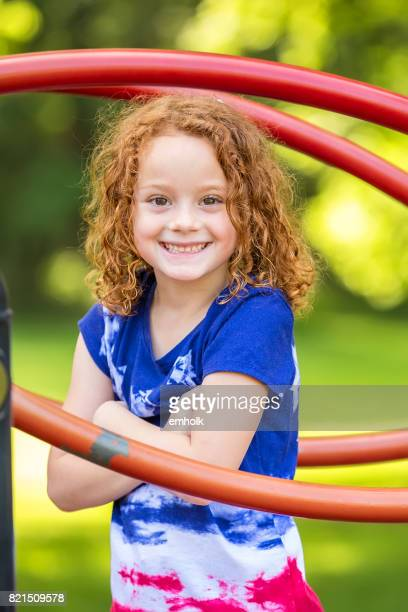 Girl With Curly Red Hair Smiling at Camera