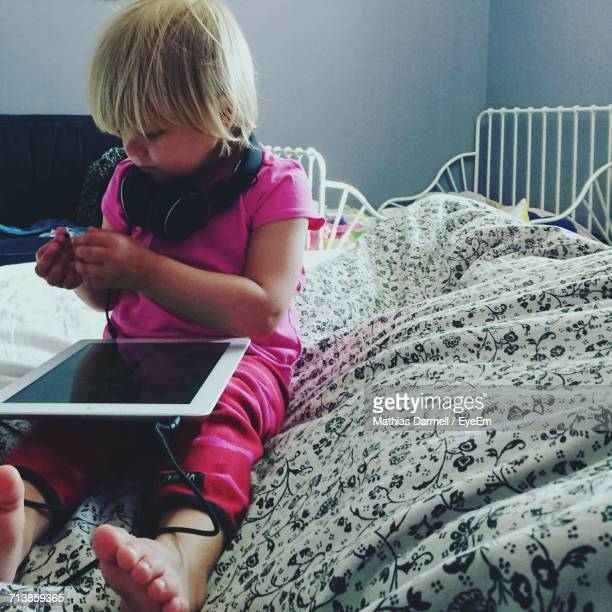 Girl With Digital Tablet And Headphones Sitting On Bed At Home