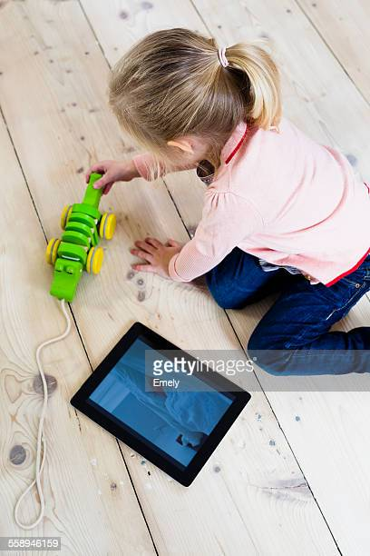 Girl with digital tablet, playing toy on wooden floor