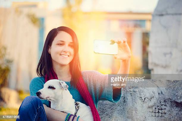 Girl with dog taking a selfie in the park