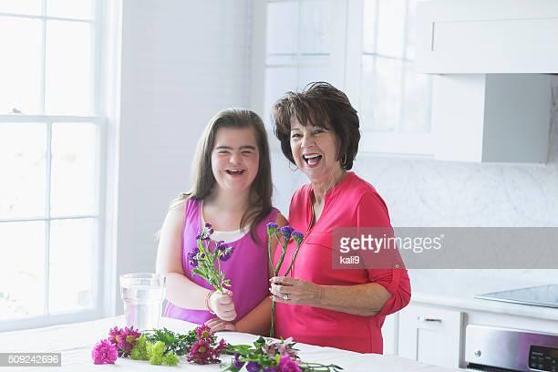 Mädchen mit down-Syndrom und Großmutter arrangieren Blumen