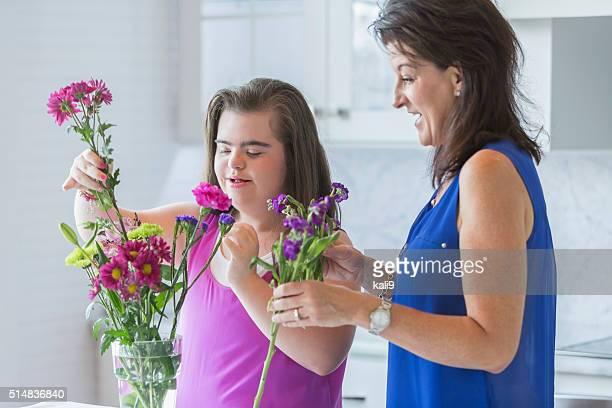 Mädchen mit down-Syndrom und Mutter arrangieren Blumen