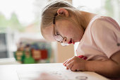 Girl with down syndrome studying at table