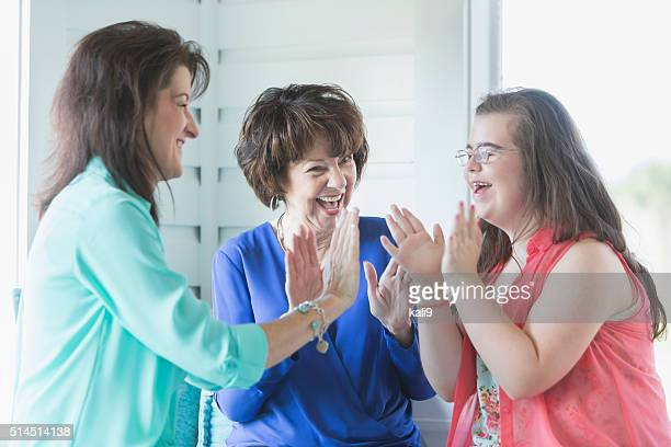 Girl with downs syndrome, mother, grandmother playing