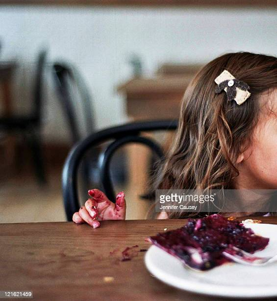 Girl with eating pie on table