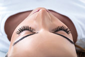 Young Girl with extended silk eyelashes lies in a beauty studio. Make up concept