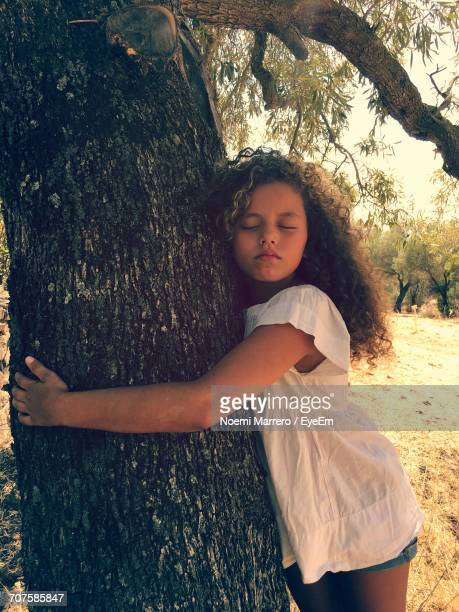 Girl With Eyes Closed Hugging Tree Trunk