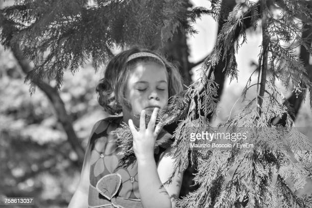 Girl With Eyes Closed Standing By Leaves