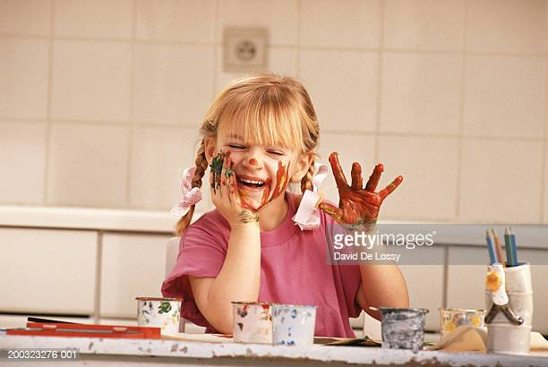 Girl (6-7) with face on paint, smiling