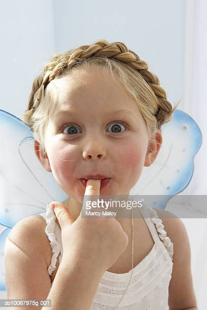 Girl (4-5) with fairy wings licking finger, portrait