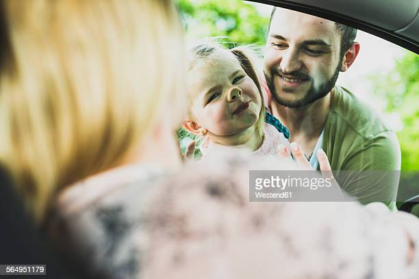 Girl with father looking at mother in car