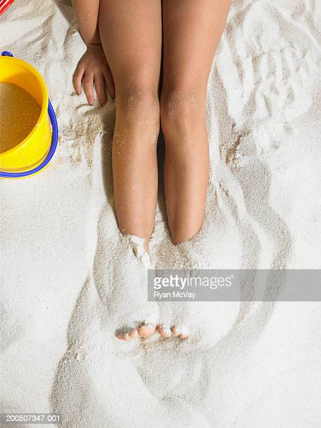 Girl (5-7) with feet buried in sand, low section, overhead view