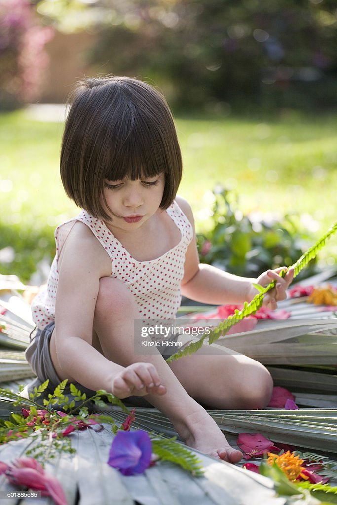 Girl with fern making flower and leaf display in garden