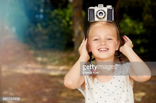 Girl with film camera on head looking at camera smiling