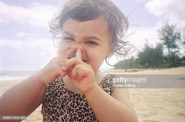 Girl (1-3) with fingers in nose, on beach, close-up, portrait