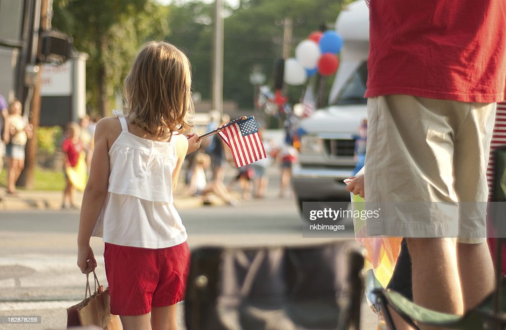 Girl with flags watches 4th of July parade in America