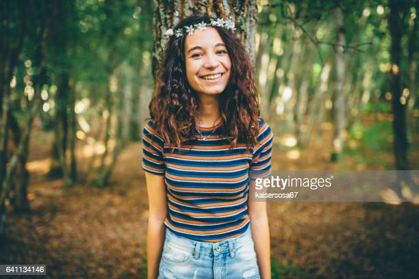 Girl with floral crown enjoying nature in the forest