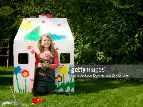 A girl with flowers and a wendy house : Stock Photo