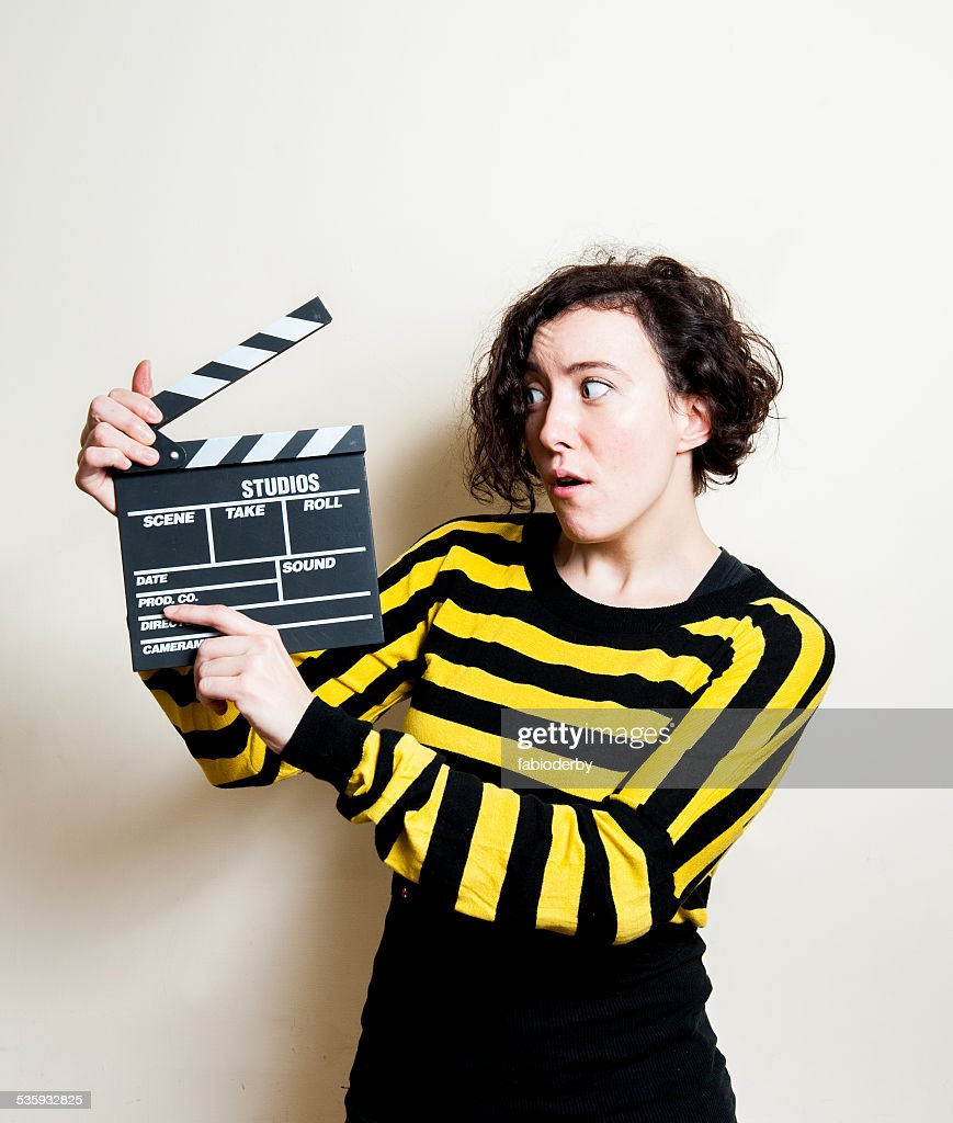 Girl with funny face and movie clapper on white background : Stock Photo