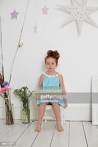 Girl with gift box against white wall with stars