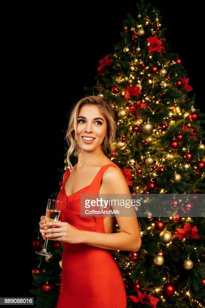 Girl with glass of sparkling wine in front of Christmas tree