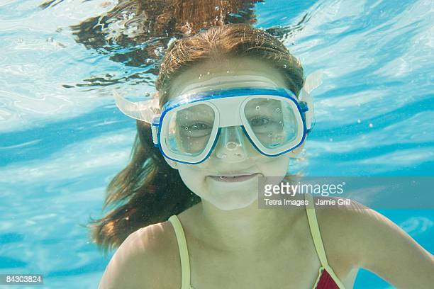 Girl with goggles swimming underwater