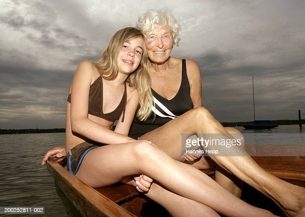 Girl (10-12) with grandmother in rowboat, portrait