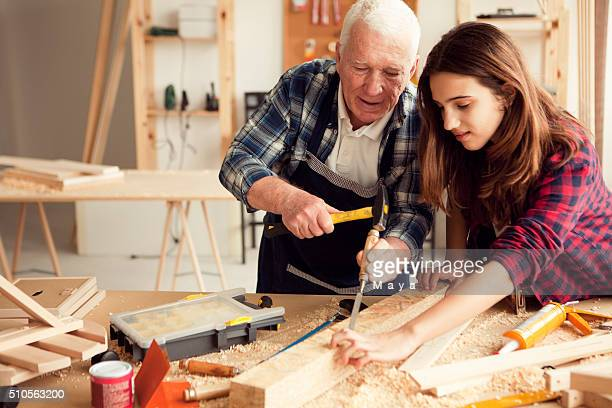 Girl with grandpa at workshop