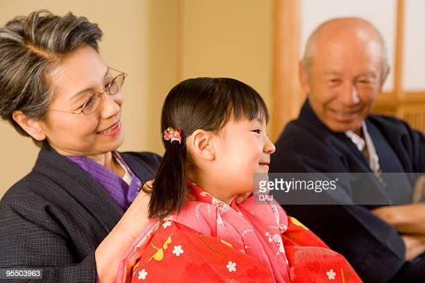 Girl with grandparents in Yukata, smiling
