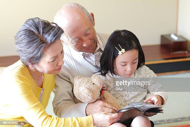 Girl with grandparents looking at brochure